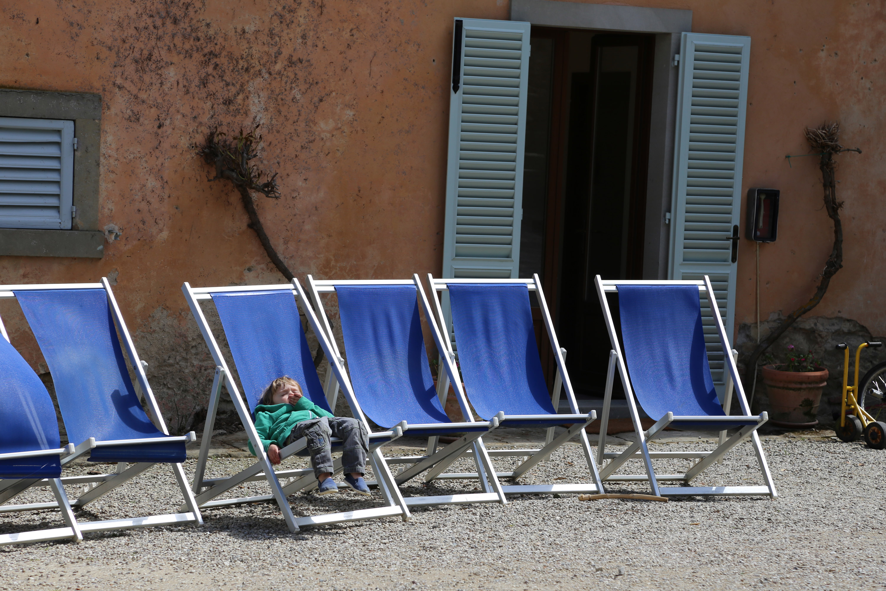 child sleeping on the deckchairs