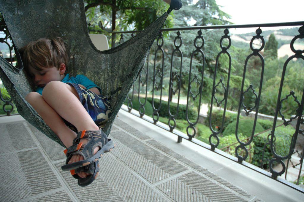 child sleeping on a balcony