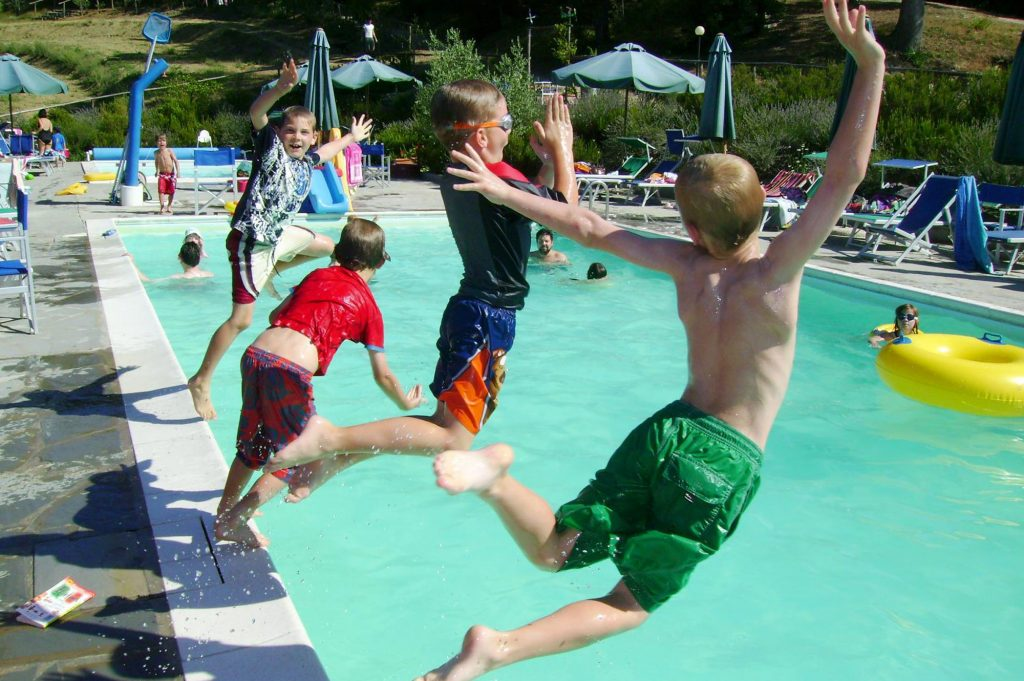boys jumping in the swimming pool