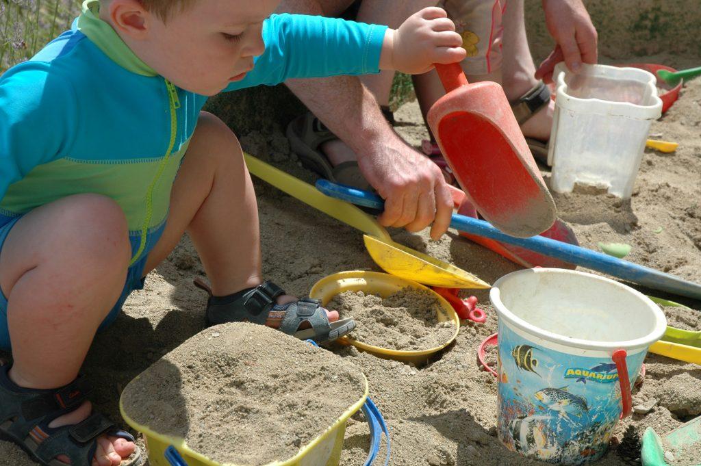child making a sandcastle in the sandpit